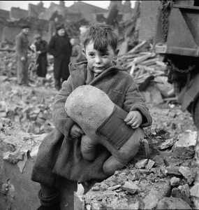 An abandoned boy, holding a stuffed toy animal amid ruins following a German aerial bombing of London in 1940